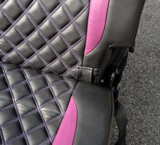 black and pink stitched leather seat closeup