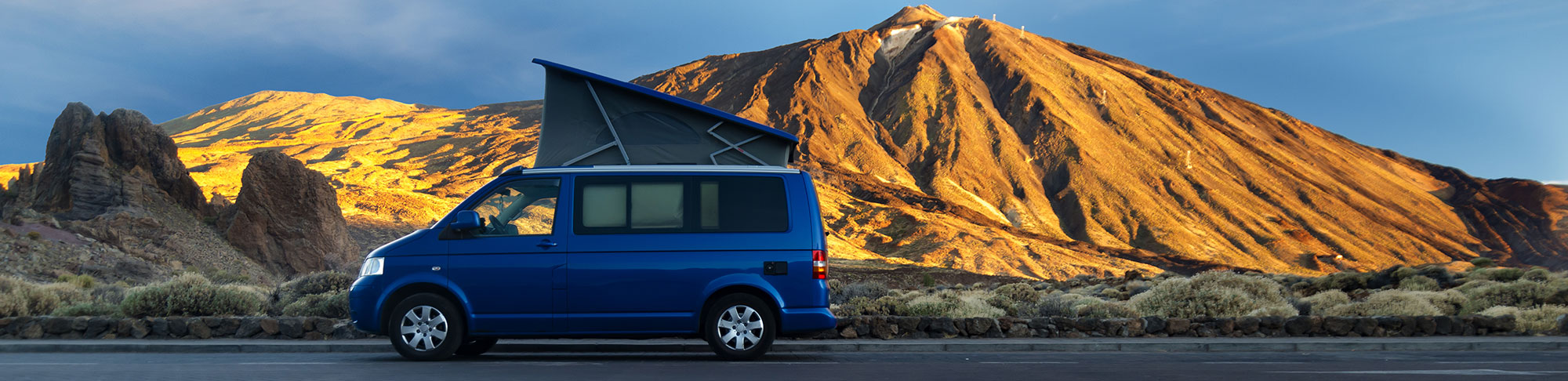 blue campervan head open parked on road by hill range