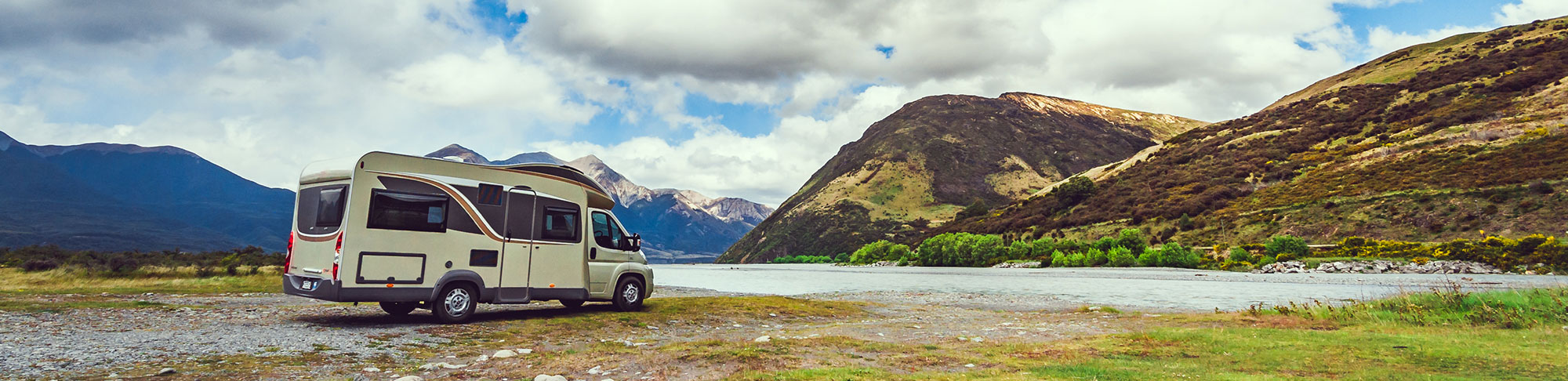 campervan parked at the base of a mountain range cloudy sky