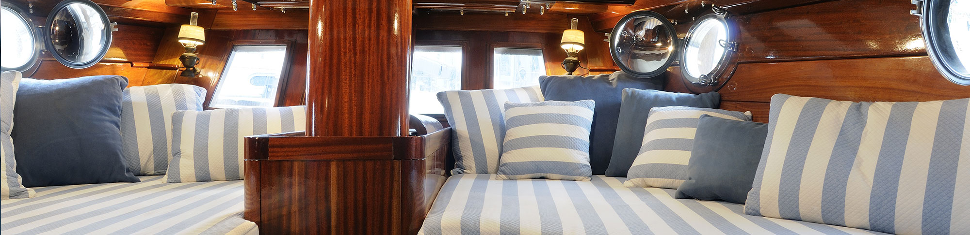 striped blue and white cushions and seating in boat cabin