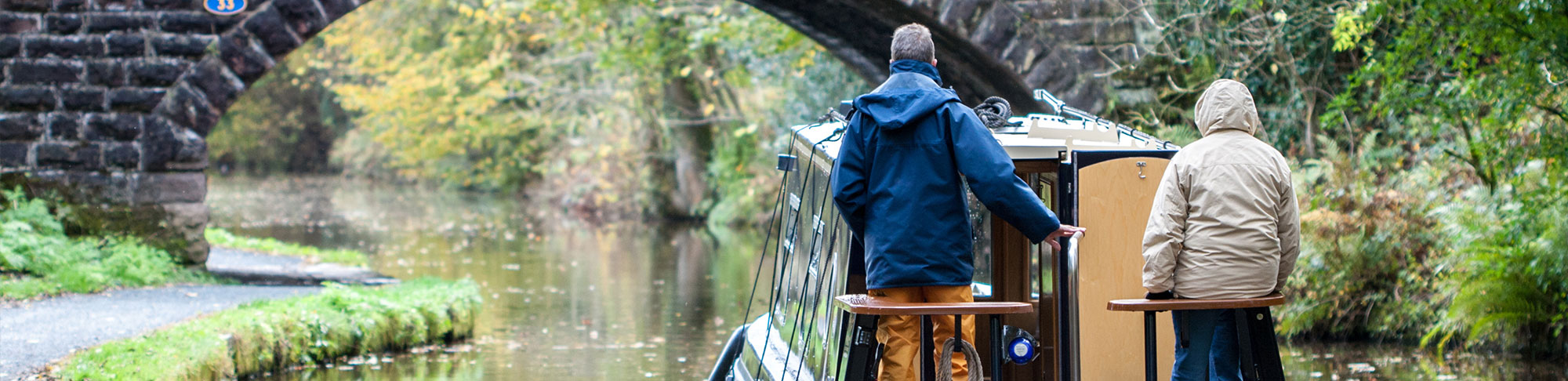 2 people stood at the back of narrow houseboat guiding boat under bridge