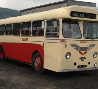 red and cream coloured vintage bus